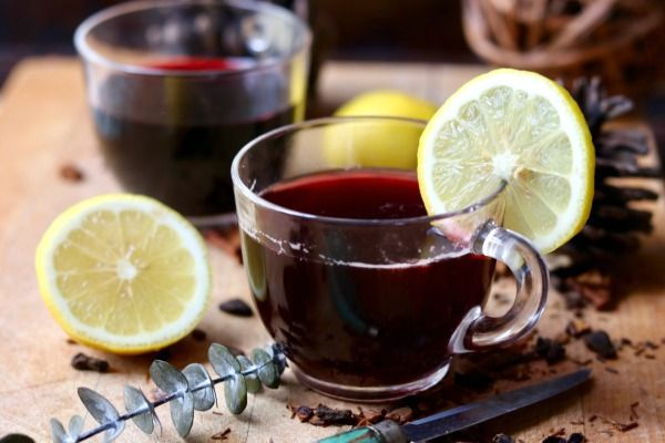 Horizontal image of low carb hot mulled wine in two punch cups garnished with lemon slices - featured image