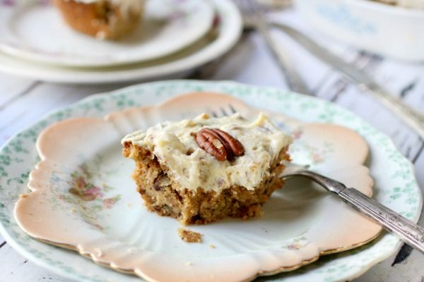 A square of pecan filled preacher cake topped with cream cheese frosting rests atop a vintage cake plate with scalloped edges. Feature image