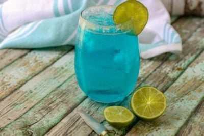 A horizontal image of a low carb cocktail, Ocean Breeze, garnished with lime. A cut lime is on the table.