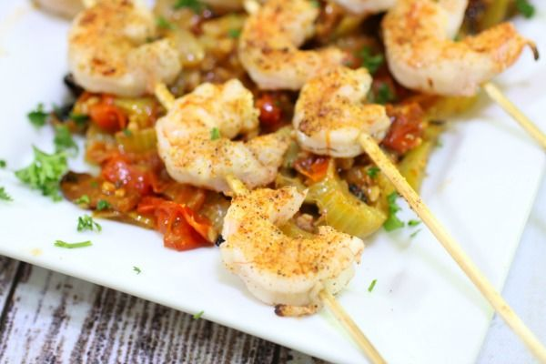 Closeup of grilled shrimp on a bed of roasted tomato relish