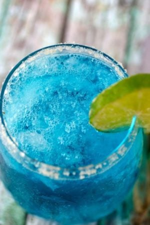 Closeup of the bright blue low carb cocktail Ocean Breeze. A lime wheel garnishes the glass.
